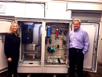 (Pictured: L-R, Nikki Wilson and Valeri Ilchenko in Tallinn, Estonia, with the N.O.W Impact Beverage Device, inside view of electrical and hydraulic cabinets).